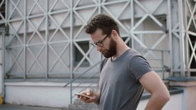 Young stylish businessman standing in street and using smartphone. Guy with beard and glasses chatting with someone. Young stylish businessman standing in the stock footage