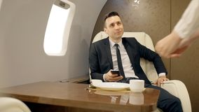 Young stylish businessman is using smartphone sitting at table in private plane. Young stylish businessman is using smartphone sitting at table in private plane stock video footage