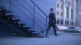 Young Stylish Businessman walking up the stairs towards office building stock video footage