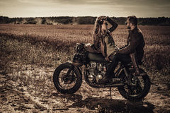 Young, stylish cafe racer couple on vintage custom motorcycles in field stock photography
