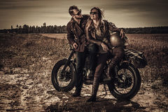 Young, stylish cafe racer couple on vintage custom motorcycles in field stock photos