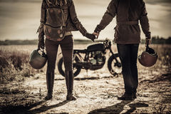 Young, stylish cafe racer couple and vintage custom motorcycles in field royalty free stock photos