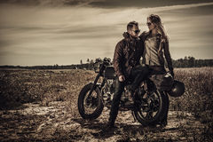 Young, stylish cafe racer couple on vintage custom motorcycles in field royalty free stock image