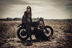 Young, stylish cafe racer couple on vintage custom motorcycles in field royalty free stock photos