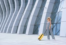 Young stylish Caucasian woman at the airport with a yellow suitcase and a straw hat. stock photo