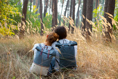 Young stylish couple with backpacks hugging in forest Stock Images