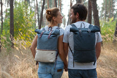 Young stylish couple with backpacks hugging in forest Royalty Free Stock Photo