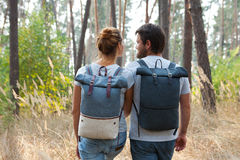 Young stylish couple with backpacks hugging in forest Stock Photo