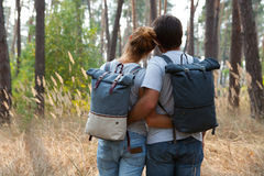 Young stylish couple with backpacks hugging in forest Stock Image