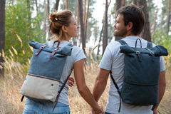Young stylish couple with backpacks hugging in forest Royalty Free Stock Photos