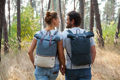 Young stylish couple with backpacks hugging in forest Stock Photos