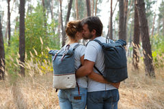 Young stylish couple with backpacks kissing in forest Stock Photos