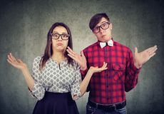 Dubious couple shrugging with shoulders. Young stylish couple in glasses looking clueless and shrugging with shoulders looking at camera Stock Photos