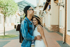 Young stylish couple hugging while standing on the street Stock Photos