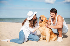 Young stylish couple in love sitting playing with dog. Young stylish beautiful couple in love sitting playing with dog Stock Image