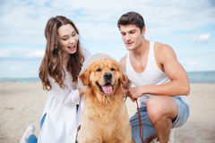 Young stylish couple in love sitting playing with dog. Young stylish beautiful couple in love sitting playing with dog Stock Photos
