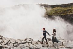 Young stylish couple in love in wool sweaters together near Dettifoss waterfall