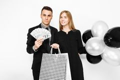 Young stylish couple, a man in a suit and a girl in a black dress, in her hands, balloons and bags, for shopping, a man holding c stock photos
