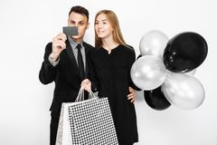 Young stylish couple, a man in a suit and a girl in a black dress holding balloons and bags, shopping, a man holding a credit car royalty free stock images