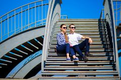 Young stylish Couple sits on stairs in sunny day. Street style Stock Images