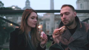 Young stylish couple sitting at the city centre and eating sandwiches in evening. Looks aside together. Young stylish couple sitting at the city centre and Stock Image