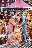 A stylish couple wearing warm clothes holding hands and looking down at a Christmas fair. A young stylish couple wearing warm clothes holding hands and looking stock image