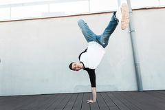 Young stylish dancer man in jeans in a fashionable shirt is standing on the hand outdoors. Handsome guy dancing break dance. Near the white wall stock photography