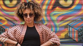 Young stylish ethnic woman against graffiti. Portrait of trendy black woman with Afro hairstyle wearing ethnic summer clothes with sunglasses holding hands on stock video footage