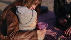 Young stylish family in casualwear sitting on plaid by waterside and having hot drinks at picnic. Mother gives a cup of. Tea to her son. Cold weather, weekend stock video