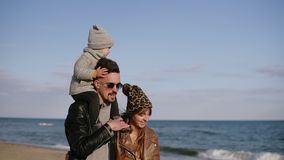 A young stylish father in sunglasses carries his son in his shoulder, a young family walk by seashore, enjoy a joint. Weekend in nature. A woman in love looks stock video footage