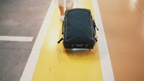 Young stylish female traveler walking across the airport parking place with suitcase. Girl come on vacation. Royalty Free Stock Image