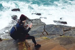 Young stylish female watching photos on cell telephone while sitting on a rock near ocean stock image