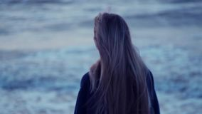 Beautiful girl looks towards the sea and turns to camera, her hair develops, wind, waves against the backdrop stock video