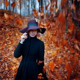 Young stylish girl in coat and hat, autumn clothing, the portrait on the background of yellowing leaves Stock Image