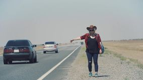 Young stylish girl in cowboy clothes doing hitch-hiking in desert, on the road. She carries backpack and hat. Pass stock video footage
