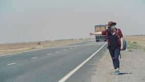 Young stylish girl in cowboy clothes doing hitch-hiking in desert, on the road. She carries backpack and hat. Pass