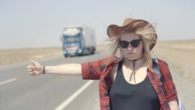 Young stylish girl in cowboy clothes doing hitch-hiking in desert, on the road. She carries backpack and hat. Pass. Trucks, delivery trucks. California or stock video