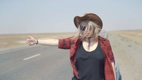 Young stylish girl in cowboy clothes doing hitch-hiking in desert, on the road. She carries backpack and hat. Pass. Trucks, delivery trucks. California or stock video footage