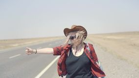 Young stylish girl in cowboy clothes doing hitch-hiking in desert, on the road. She carries backpack and hat. Pass stock footage