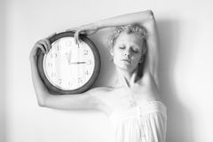 Young stylish girl with curly hair and a big clock in his hands Stock Photography