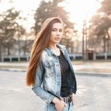 Young stylish girl in denim clothes at sunset. Royalty Free Stock Images