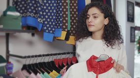 Girl choosing between two pieces of cloth in a store. Young stylish girl holding two colorful jackets standing and putting them on her body to see how it looks stock video footage