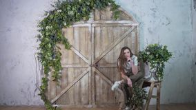 Young stylish girl posing against the wooden gate, smiling and looking at the camera royalty free stock photos