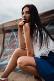 Young stylish girl sitting near a concrete wall which is all covered in graffiti royalty free stock photo
