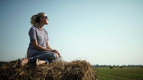 Young stylish girl in a striped t-shirt sitting on a haystack. stock video