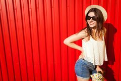 Young stylish girl wearing glasses and hat with flowers against red wall. Summer outfit. Fashion. Copy space. Happy stylish girl wearing glasses and hat with stock image