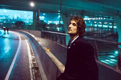 Young stylish guy on the background of night city, city lights royalty free stock image