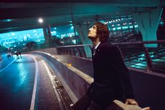 Young stylish guy on the background of night city, city lights royalty free stock photo