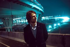 Young stylish guy on the background of night city, city lights royalty free stock photography