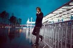 Young stylish guy on the background of night city, city lights royalty free stock photos